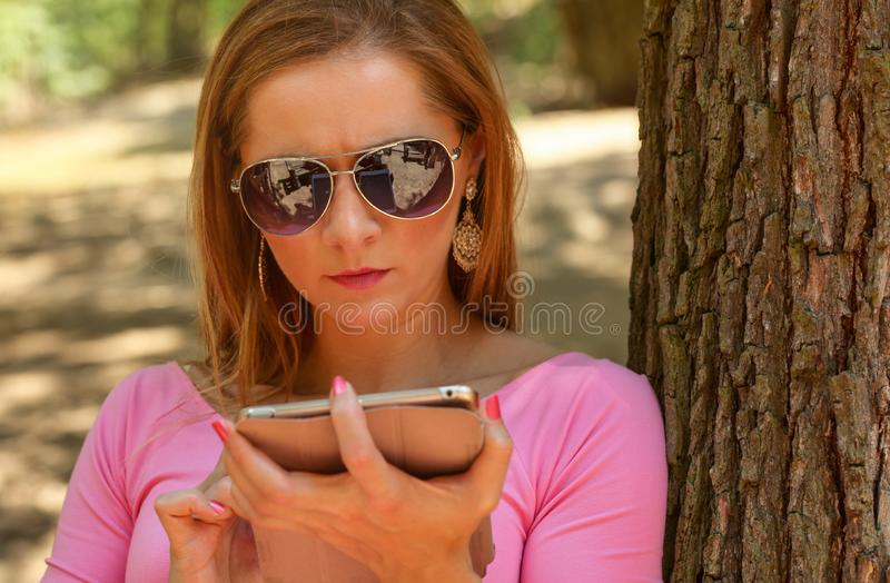 Young woman in sunglasses, sitting on a bench in park, working w. Ith tablet. Detail on her head royalty free stock images
