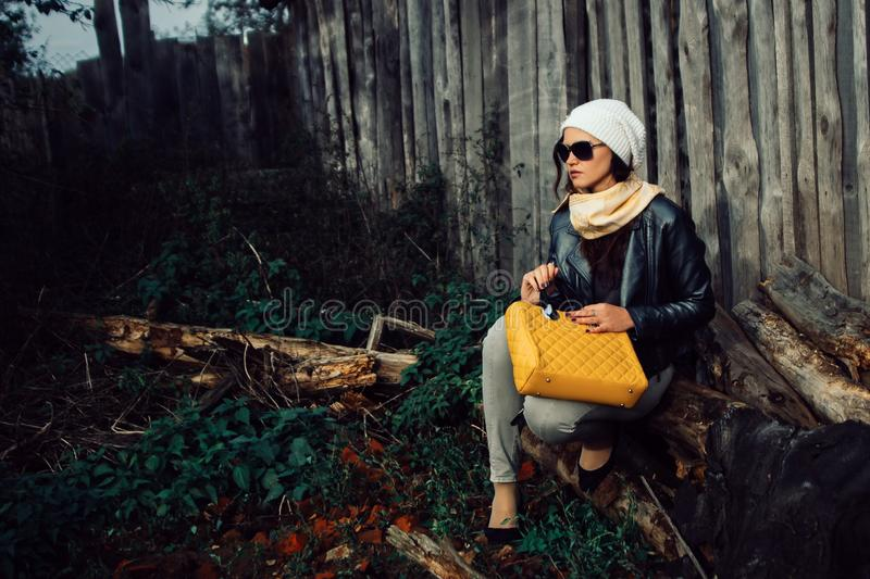 Young woman in sunglasses sitting near an old barn royalty free stock image