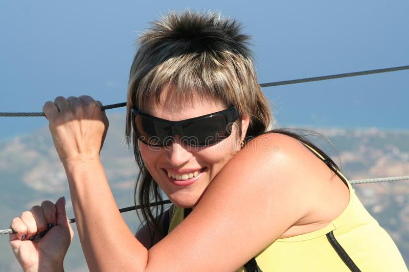 Young woman in sunglasses is smiling, standing on the edge of the cliff and holds on by hands for enclosure from steel ropes royalty free stock photo