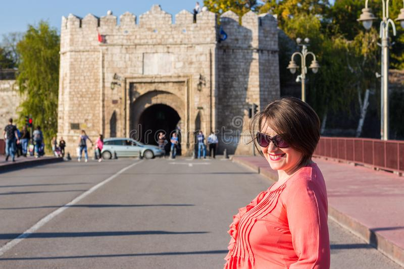 Young Woman With Sunglasses Standing on the Bridge in the Middle of the Street and Smiling stock images