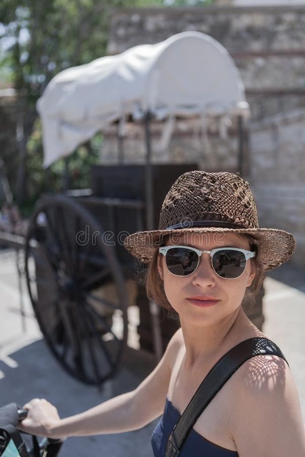 The young woman in the sunglasses and straw hat royalty free stock photos