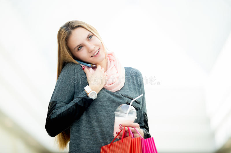 Young woman in supermarket talking on mobile phone holding shopping bags and strawberry cocktail royalty free stock photos