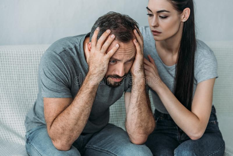 young woman supporting depressed frustrated boyfriend royalty free stock photos