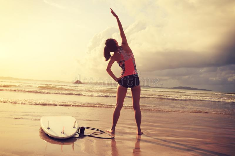 Woman surfer warming up on beach royalty free stock photos