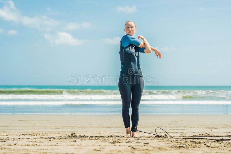 Young woman surfer warming up on the beach before surfing.  royalty free stock photo