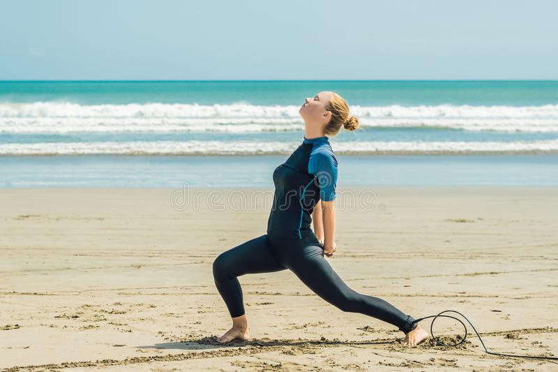 Young woman surfer warming up on the beach before surfing.  stock photos