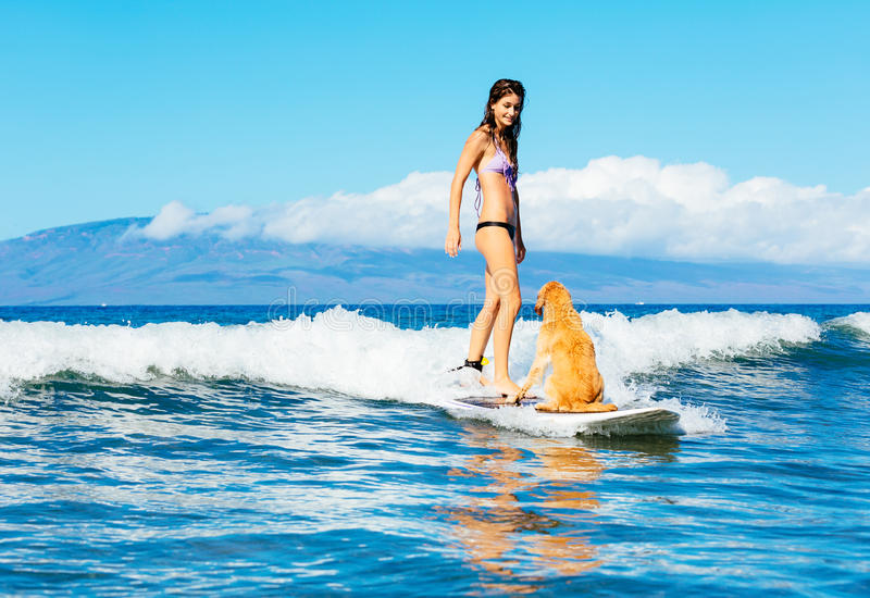 Young Woman Surfing with Her Dog. Attractive Young Woman Surfing with her Dog. Sharing surfboard with Golden Retriever royalty free stock photo