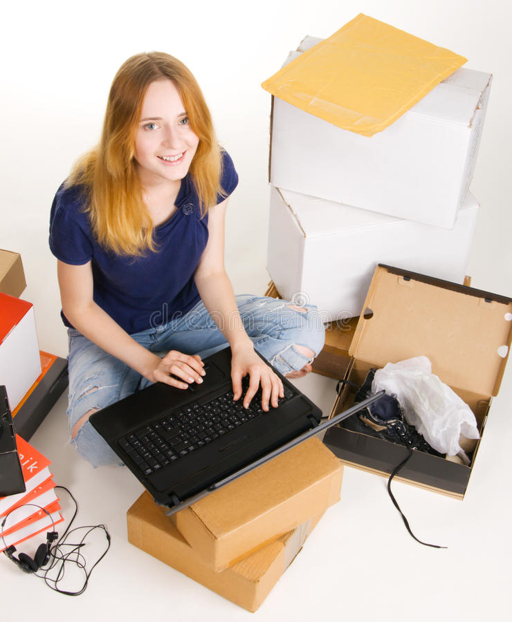 Young woman surfing an online store. Young beautisul woman surrounded by delivered orders, surfing an online store at her laptop royalty free stock photography