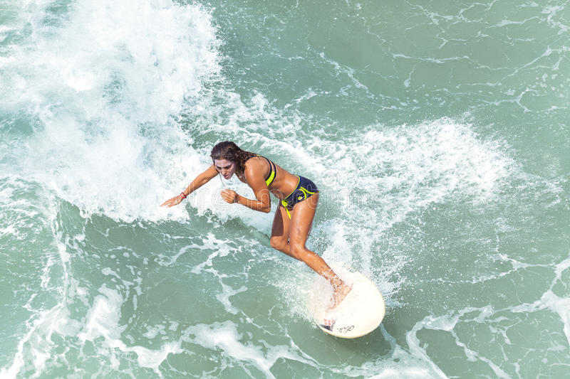 Young woman surfing. Venice, California, USA - August 22, 2015: Young woman surfing at Venice Beach on a beautiful sunny day royalty free stock images