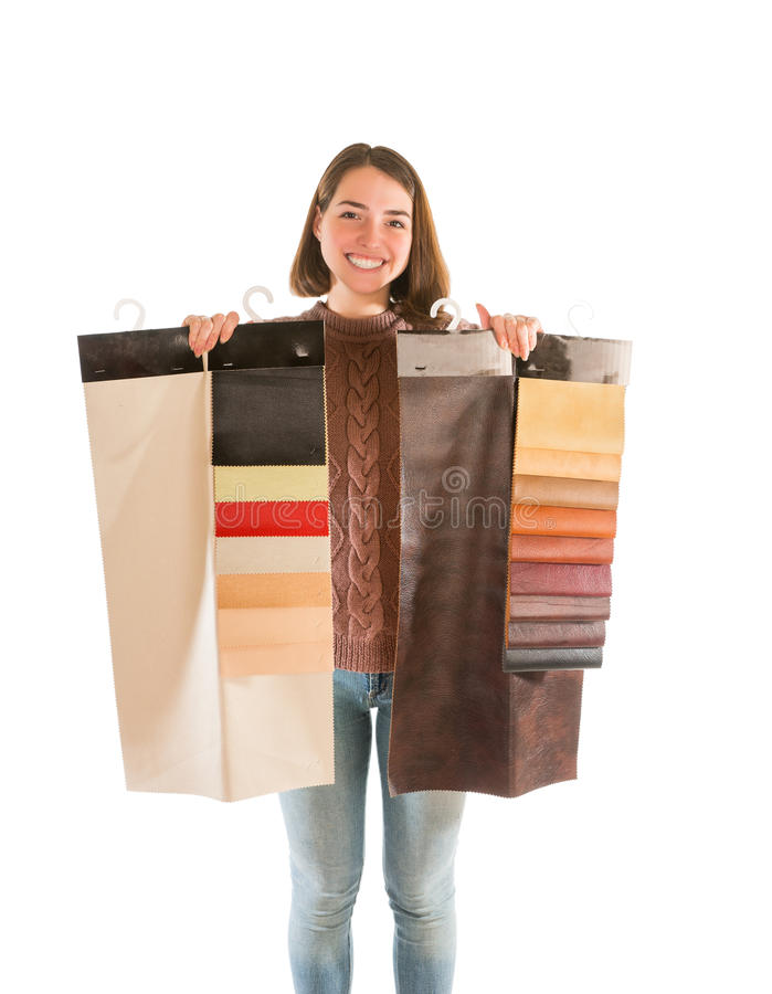 Young woman in sweater holding fabric swatches. Isolated on white background stock photo