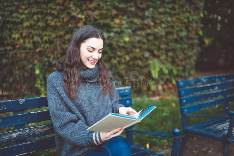 Woman reading a book on the bench in a park royalty free stock photos