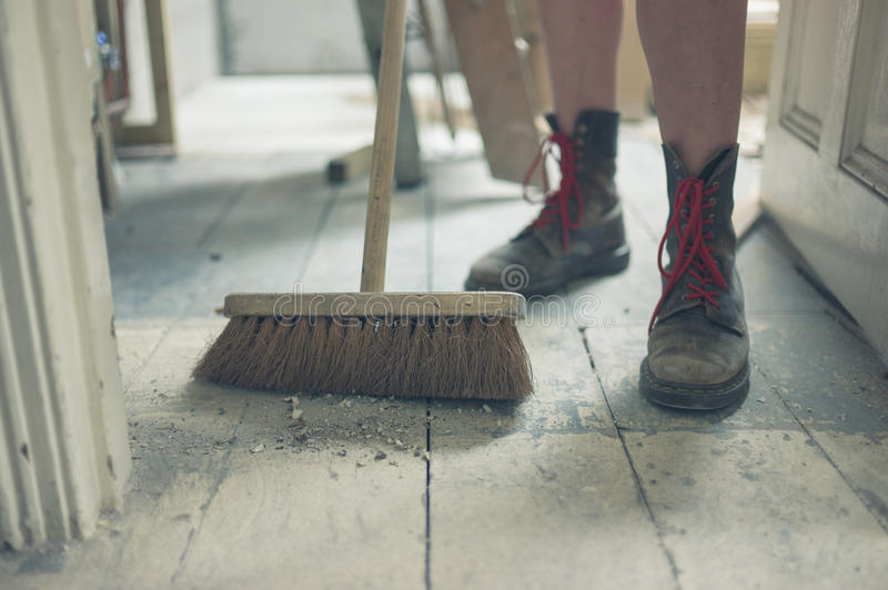 Young woman sweeping the floor royalty free stock photography