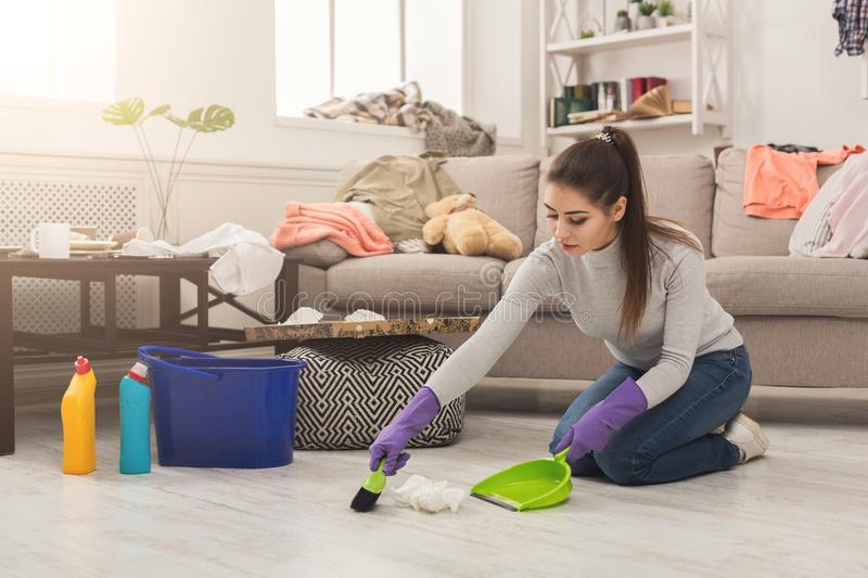 Young woman sweeping floor in messy room royalty free stock photo