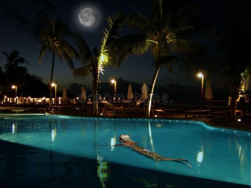 Young woman swimming. Beautiful night pool royalty free stock photos