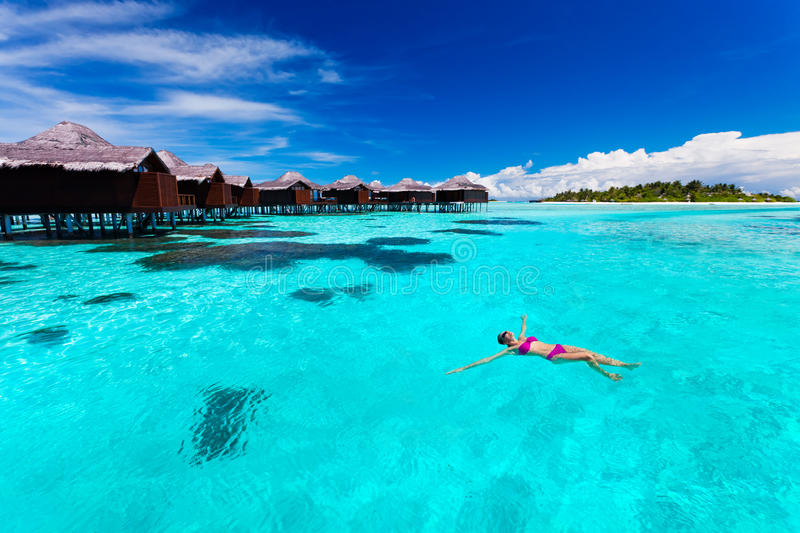 Young woman swimming from hut in tropical lagoon. Young woman swimming from hut in blue tropical lagoonYoung couple snorkling from hut over blue tropical lagoon royalty free stock photography