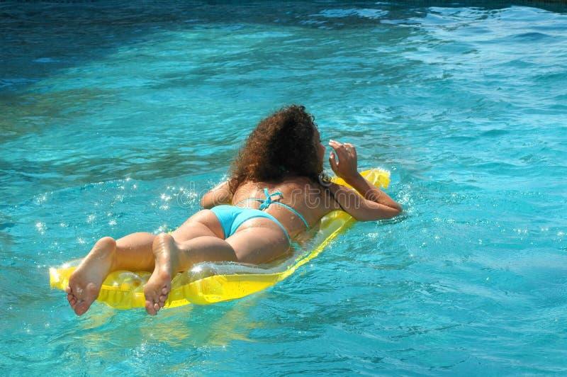 Young woman swimming on mattress royalty free stock photo