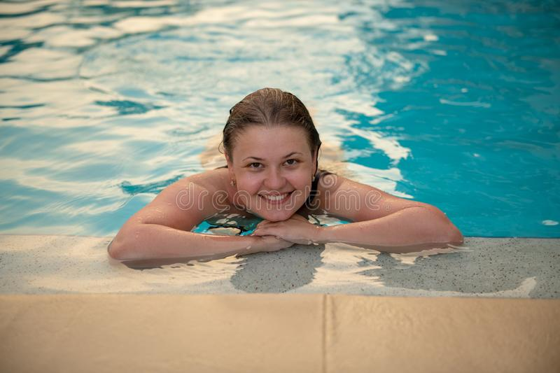 Young woman in swimming pool. Summer portrait of a beautiful sexy girl in a swimming pool royalty free stock images