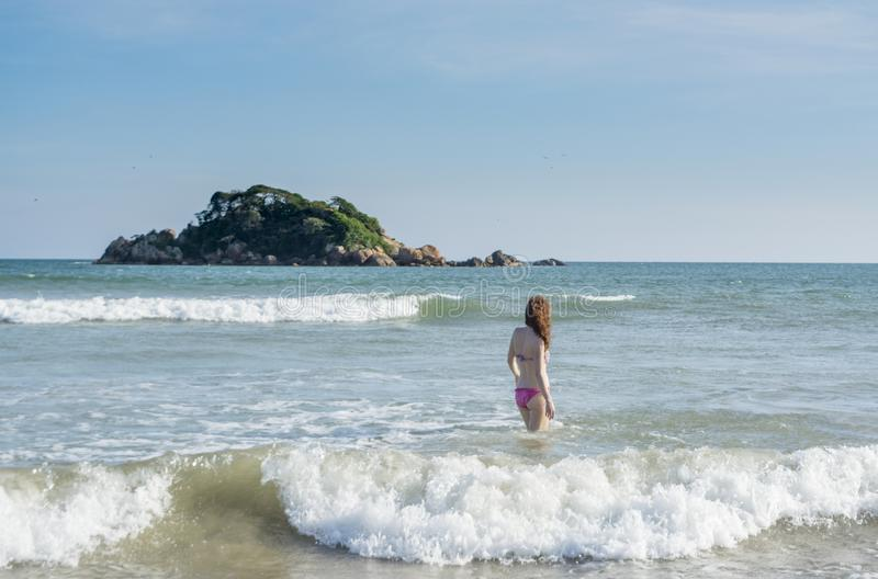 Young woman in swimming suit going into ocean on the beach in Weligama. In Sri Lanka stock images