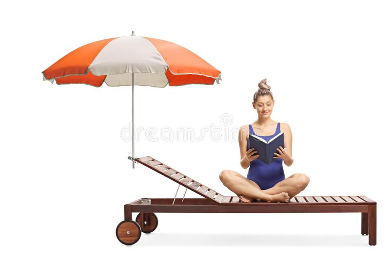 Young woman in a swimming suit sitting on a sunbed under umbrella and reading a book stock image