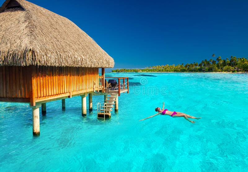 Young woman swimming in tropical lagoon next to overwater villa. Woman swimming in tropical lagoon next to overwater villa stock image