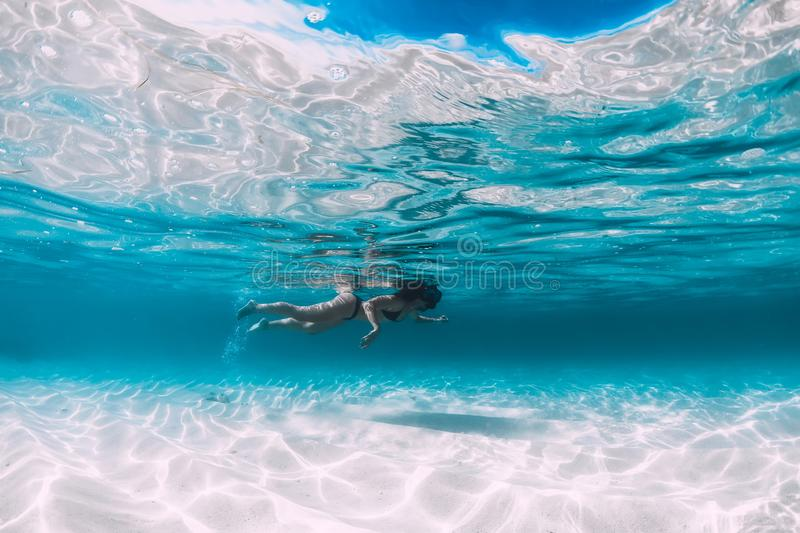 Young woman swimming underwater in the tropical blue ocean with sand stock photos