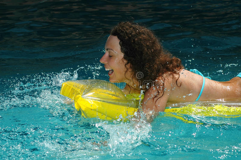 Young woman swimming in water pool stock photo
