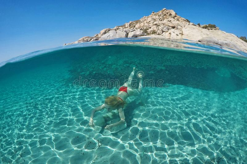 Young woman swims on half underwater royalty free stock image