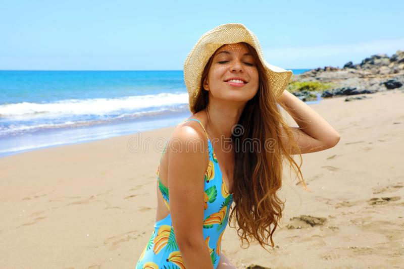 Young woman in swimsuit enjoying on beach. Attractive young woman with closed eyes and hat kneeling on a beach.  royalty free stock images