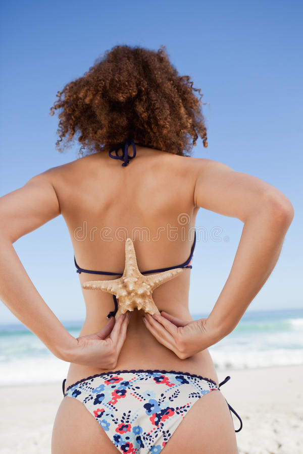 Download Young Woman In Swimsuit Holding A Starfish Stock Photo - Image: 25333272