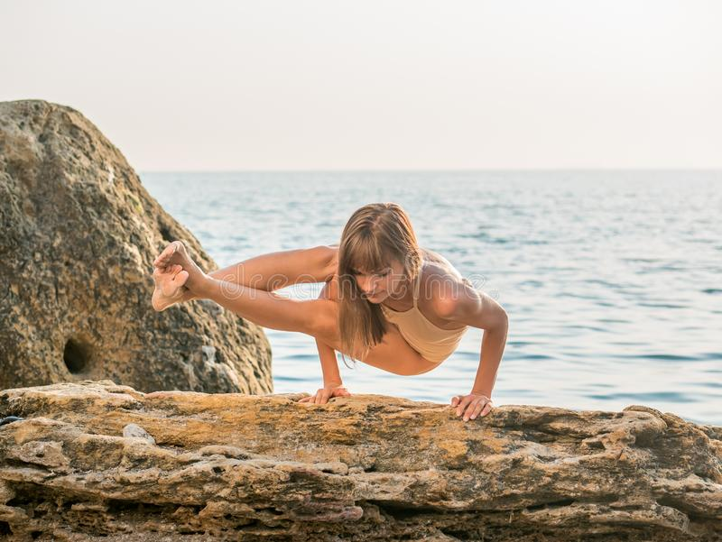Young woman in swimsuit practicing yoga at amazing sunrise. Fitness, sport, yoga and healthy lifestyle concept. Girl stock photo