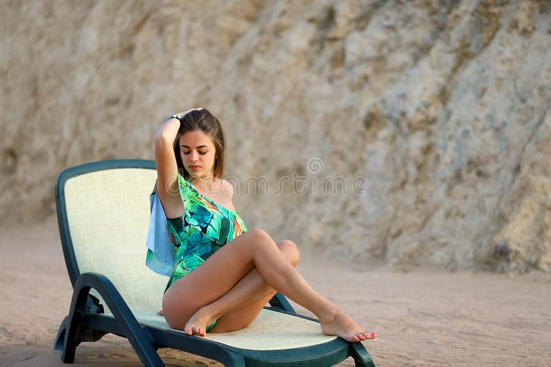 A young woman in a swimsuit relaxing on a deckchair on the beach. Close-up of sensual young girl without makeup. In the midst of nature. Summer Vacation Concept royalty free stock photo