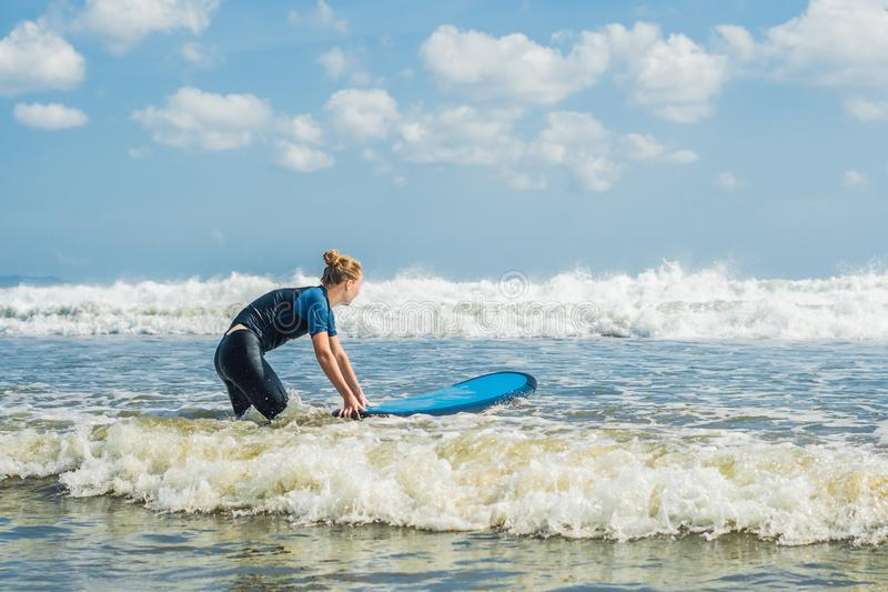 Young woman in swimsuit with surf for beginners ready to surf. P. Ositive emotions royalty free stock image