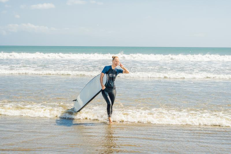 Young woman in swimsuit with surf for beginners ready to surf. P. Ositive emotions stock image