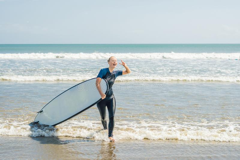 Young woman in swimsuit with surf for beginners ready to surf. P. Ositive emotions royalty free stock photo