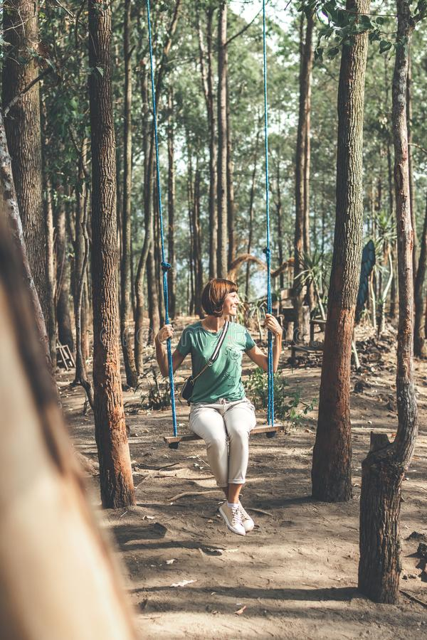 Young woman on the swing in the forest. Bali island. stock photos