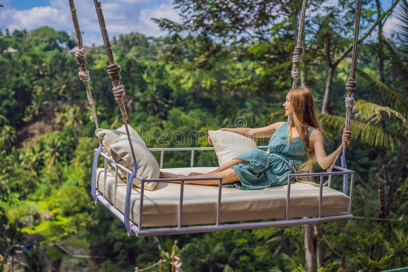 Young woman swinging in the jungle rainforest of Bali island, Indonesia. Swing in the tropics. Swings - trend of Bali.  stock image