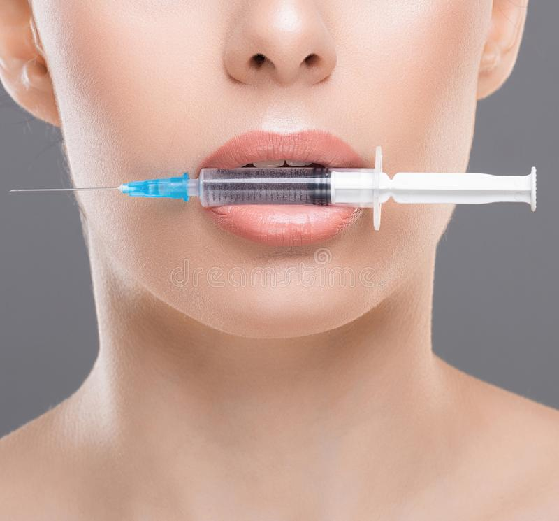 Young woman with syringe in her mouth close up. Aesthetic cosmetology and beauty injections. Young woman with syringe in her mouth close up royalty free stock photos