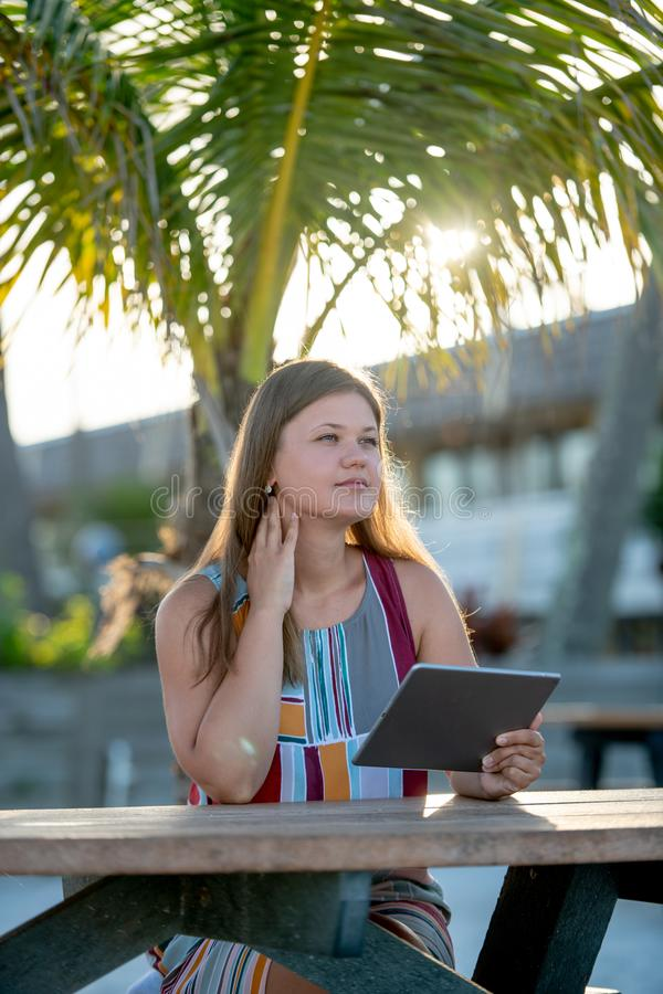 Young woman with tablet on the beach stock photo