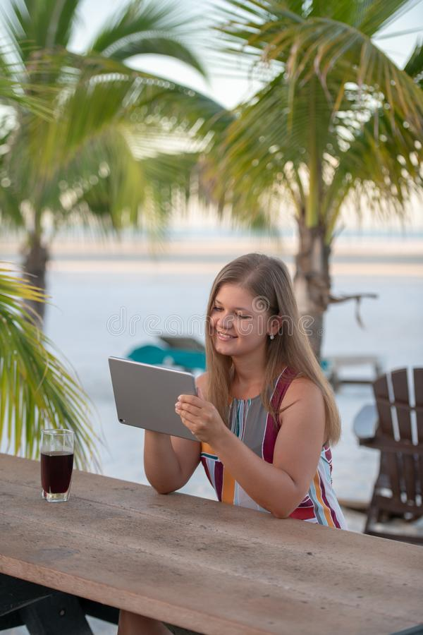 Young woman with tablet on the beach. Young woman wearing dress using tablet on the beach in the morning on the background of palm trees in Florida royalty free stock photo