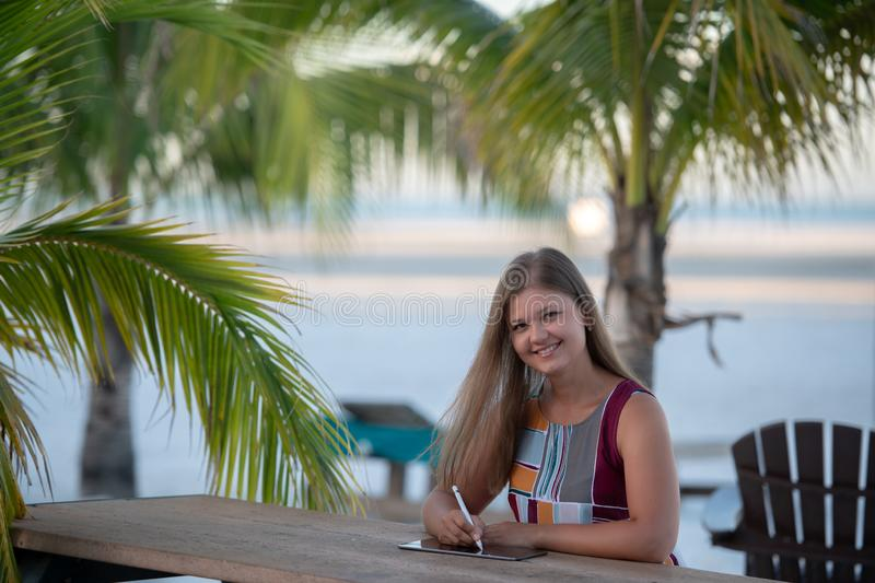Young woman with tablet on the beach. Young woman wearing dress using tablet on the beach in the morning on the background of palm trees in Florida stock photo