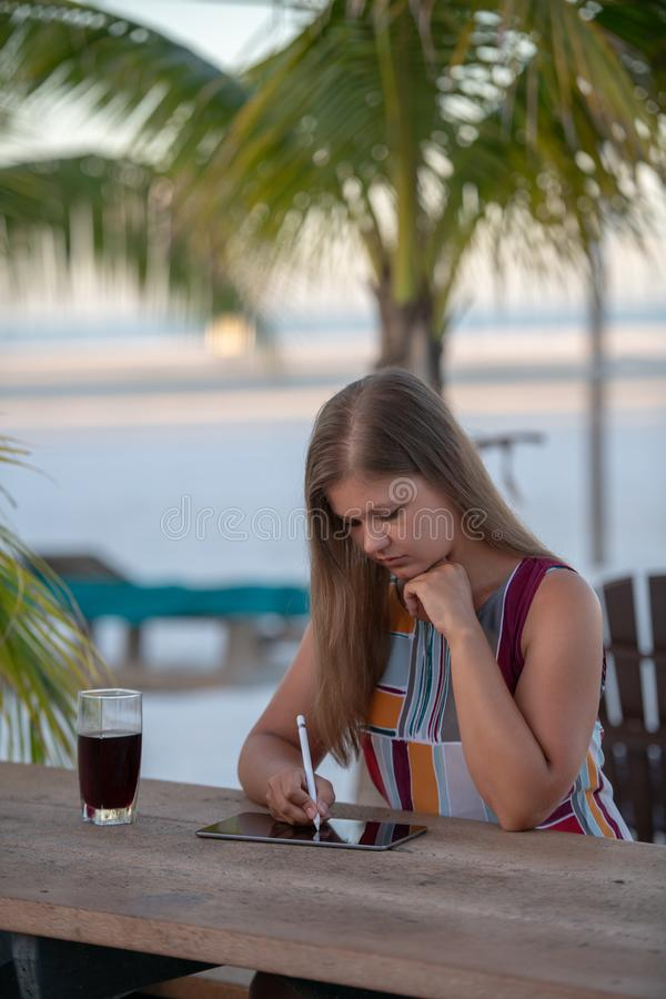 Young woman with tablet on the beach. Young woman wearing dress using tablet on the beach in the morning on the background of palm trees in Florida with glass of stock image