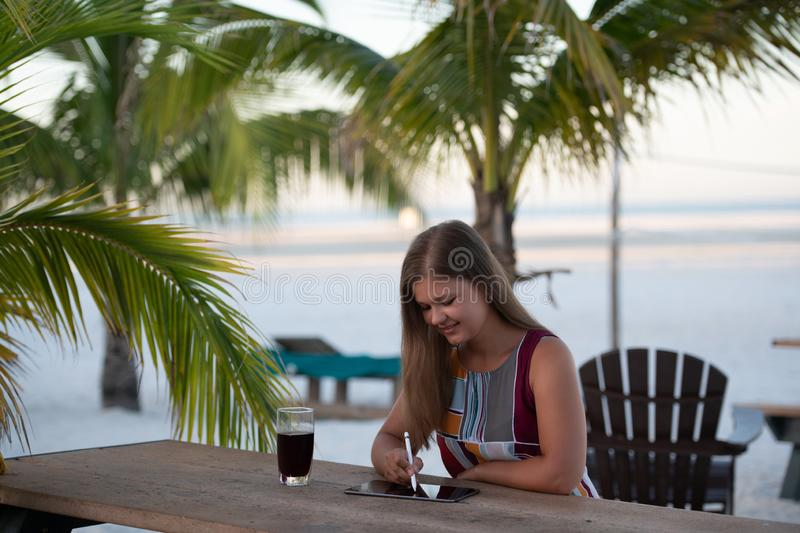 Young woman with tablet on the beach. Young woman wearing dress using tablet on the beach in the morning on the background of palm trees in Florida with glass of stock images