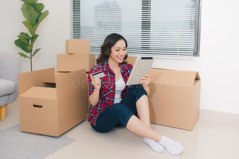 A young woman with tablet and cardboard boxes moving in a new home royalty free stock photos