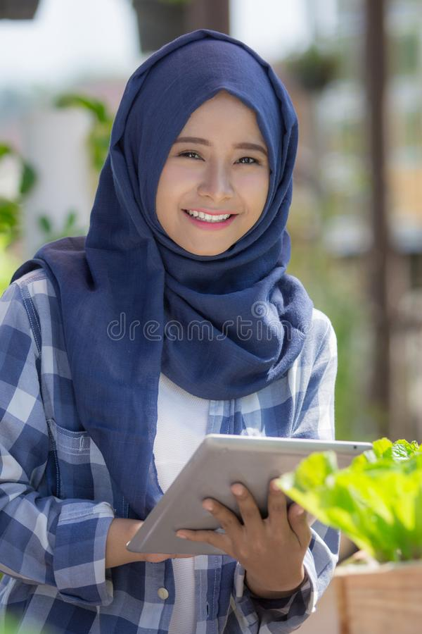 Young woman with tablet in the farm. Happy young asian woman with tablet in the farm. modern urban farming concept stock photo