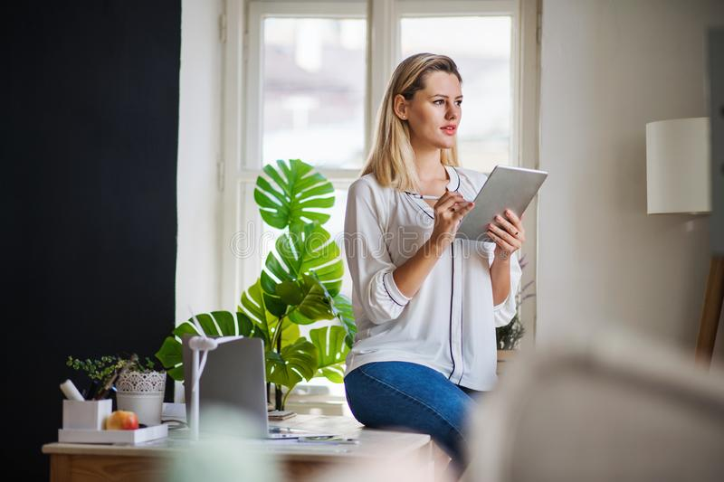 Young woman with tablet indoors in home office, working. stock image