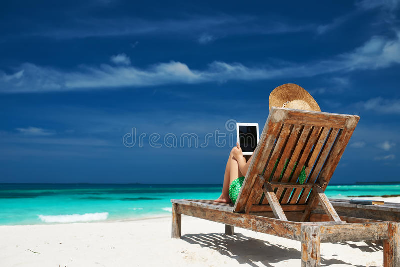 Young woman with tablet pc at the beach royalty free stock photography