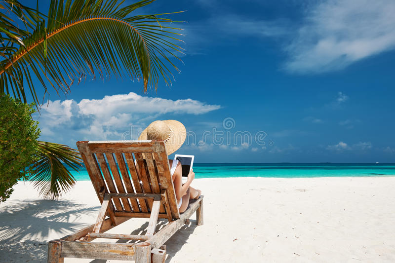 Young woman with tablet pc at the beach royalty free stock image