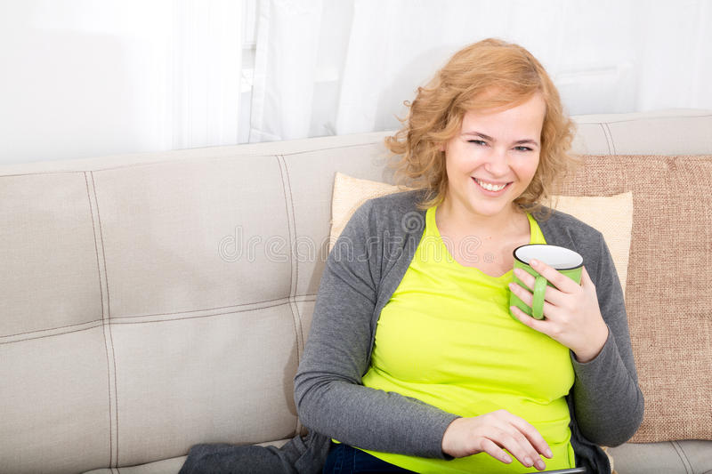 Young woman with a Tablet PC on the Sofa stock photos