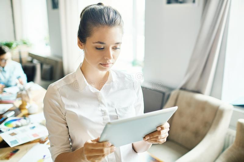 Learning fashion trends. Young woman with tablet searching in the net while looking for popular and creative trends and tendencies in modern fashion royalty free stock image