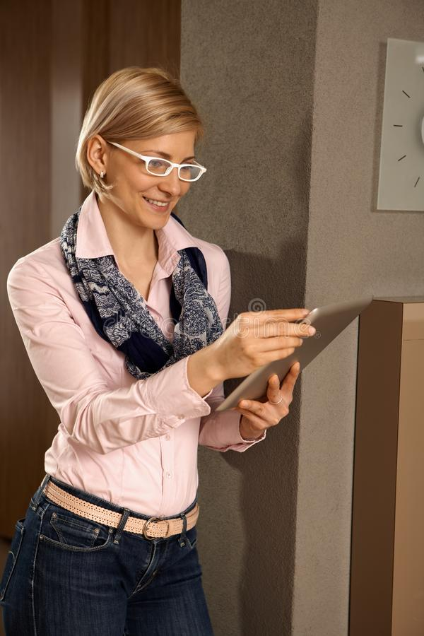Young woman with tablet. Young woman using tablet computer, smiling, standing royalty free stock photography